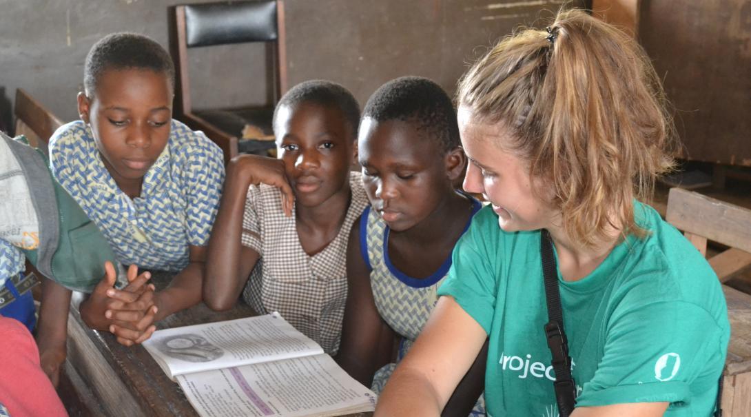 Voluntaria trabajando con niños para ayudarlos a mejorar su inglés.